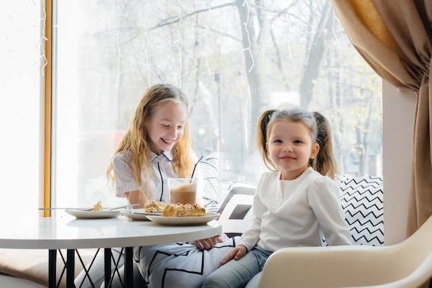 Two cute little girls are sitting in a cafe and playing on a sunny day. recreation and lifestyle.