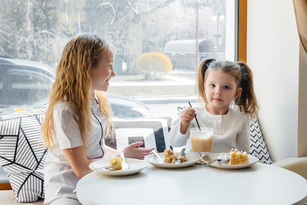 Two cute little girls are sitting in a cafe and playing on a sunny day