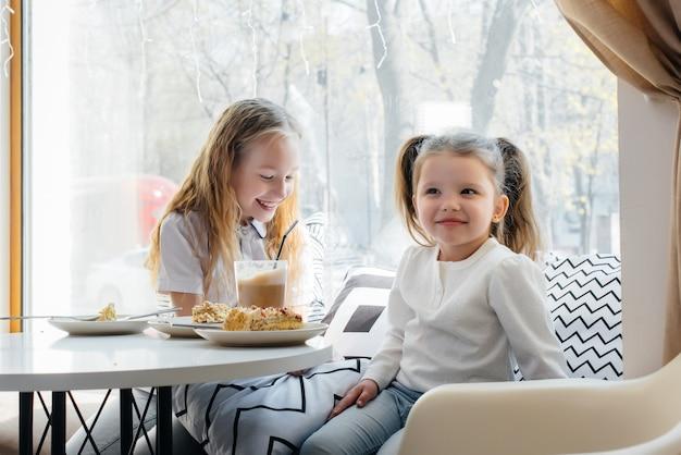 두 명의 귀여운 소녀가 카페에 앉아 화창한 날에 놀고 있습니다. 레크리에이션과 라이프 스타일.