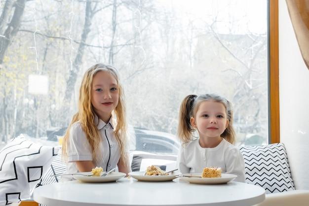 두 명의 귀여운 소녀가 카페에 앉아 화창한 날에 놀고 있습니다.