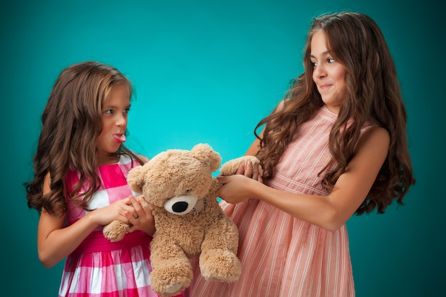 Two cute little girls on blue with teddy bear