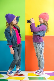 Two cute little girls making a photo on colorful wall