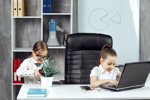 두 명의 귀여운 소녀가 사무실에서 노트북 작업을 하고 꽃에 물을 주는 사무실 직원으로 포즈를 취합니다.