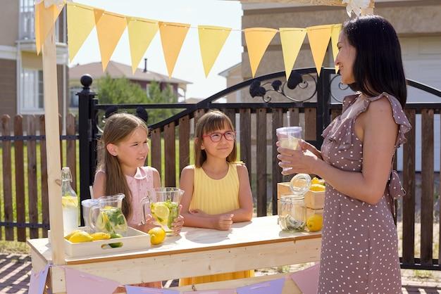 木製の屋台のそばに立って、新鮮な自家製レモネードのガラスを持っているエレガントなドレスで若いきれいな女性を見ている2人のかわいい女の子