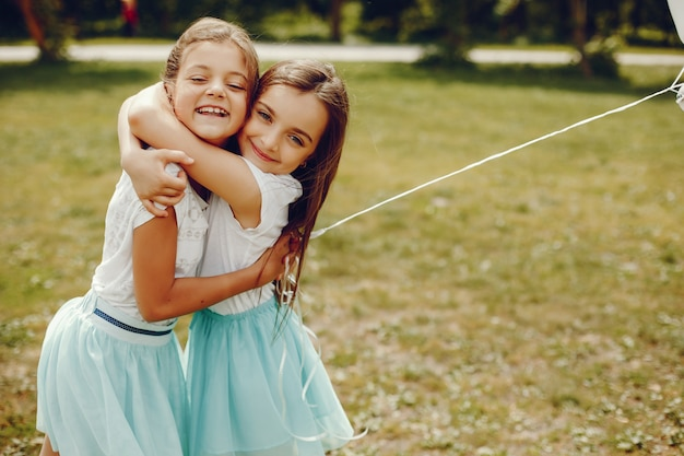 Two cute little girls in white t-shirts and blue skirts play in the summer park with balloons