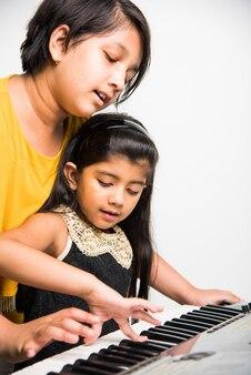 白い背景の上でピアノやキーボード、楽器を演奏する2人のかわいいインド人またはアジア人の女の子