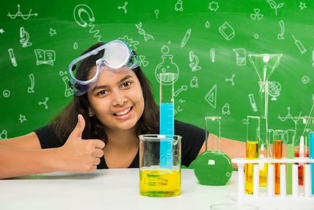 実験室で科学を実験または勉強している2人のかわいい小さなインド人またはアジア人の女子学生、教育的な落書きで緑の黒板の背景の上に