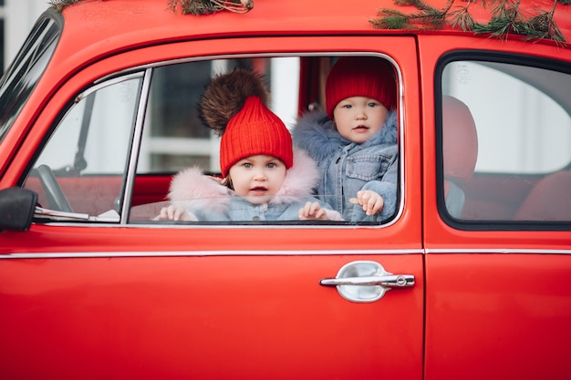 Two cute little kids in winter clothes peeking out of the window of a bright red car