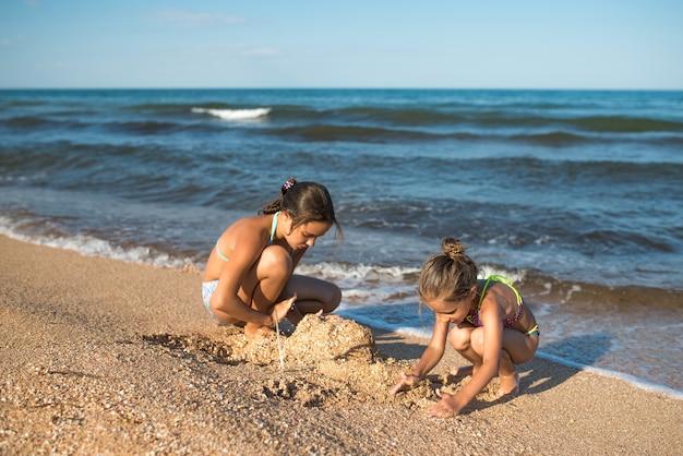 Две милые маленькие сестры играют в песке на пляже в солнечный летний день.
