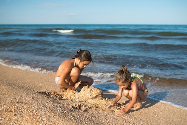 Two cute little little sisters play in the sand on the beach on a sunny summer day.