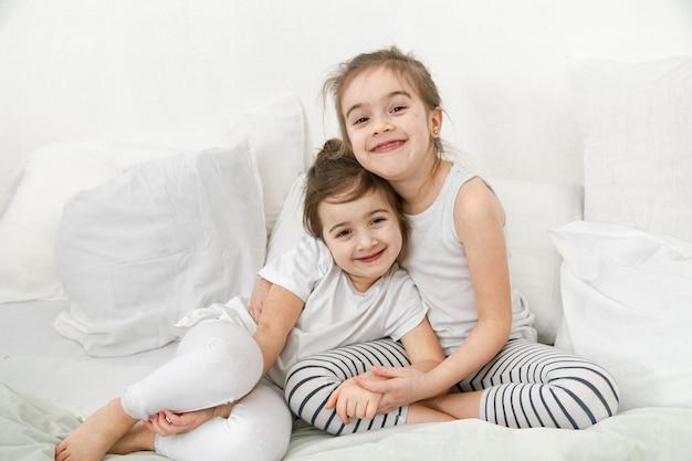 두 명의 귀여운 여동생이 침실의 침대에서 껴안고 있습니다. 가족 가치와 아이들의 우정의 개념.