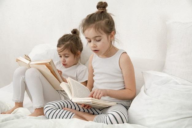 Two cute little sister girls are reading a book on the bed in the bedroom. the concept of family values and children's friendship.