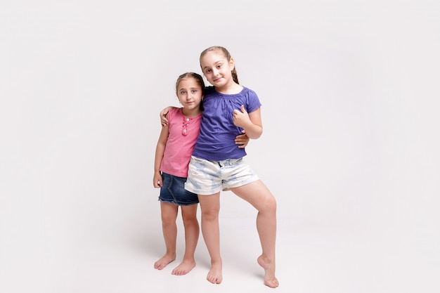 Two cute little sisters of different ages smiling showing hand gesture thumb up