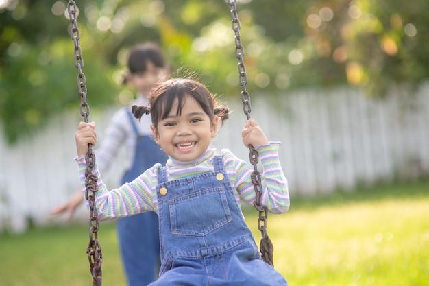 따뜻하고 화창한 날 야외에서 아름다운 여름 정원에서 함께 그네를 타고 있는 귀여운 두 자매. 아이들을 위한 활동적인 여름 레저.