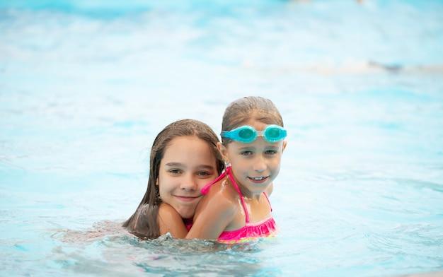 두 명의 귀여운 여동생이 수영장에서 수영