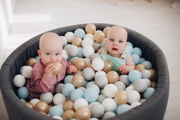 두 명의 귀여운 작은 유아가 재미있는 색색의 공을 가지고 양동이에 앉아 포즈를 취하고 있습니다. 함께 노는 활동적인 아이들은 긍정적인 감정을 가지고 있습니다.