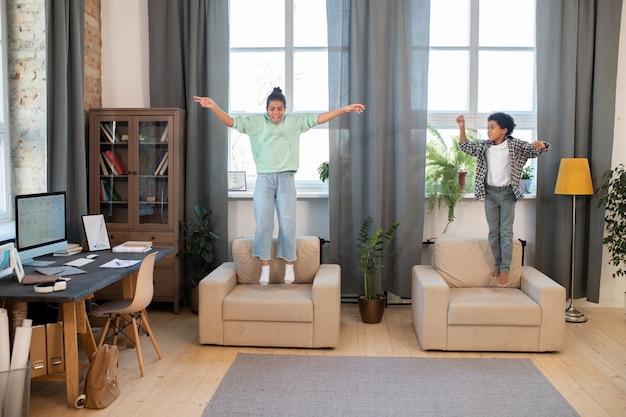 Два симпатичных брата и сестры смешанной расы в повседневной одежде прыгают на мягких креслах у больших окон в гостиной, развлекаясь после школы