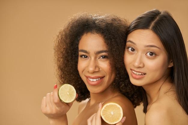 Две милые молодые женщины смешанной расы смотрят в камеру и держат нарезанный лимон и лайм