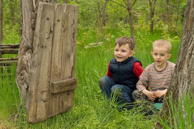 長い緑の芝生にしゃがむ 2 つのかわいい遊び心のある若い男の子