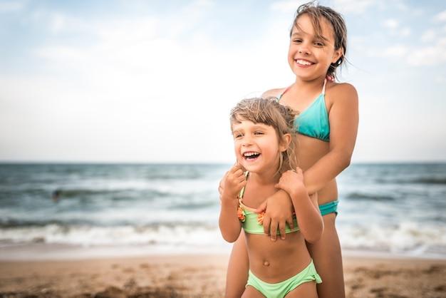 暖かい夏の日の休暇中に海で泳いでいる間、2人のかわいいポジティブな小さな女の子の姉妹が手を上げました。健康で楽しい子供たちの概念