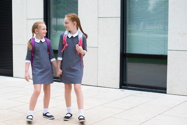 두 명의 귀여운 빨간 머리 여학생이 학교에 갑니다. 웃으면서 채팅하세요. 교복을 입은 자매. 텍스트에 대 한 장소입니다.