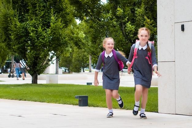 두 명의 귀여운 빨간 머리 여학생이 학교에 갑니다. 웃고, 채팅하고, 실행합니다. 교복을 입은 자매. 텍스트에 대 한 장소입니다.