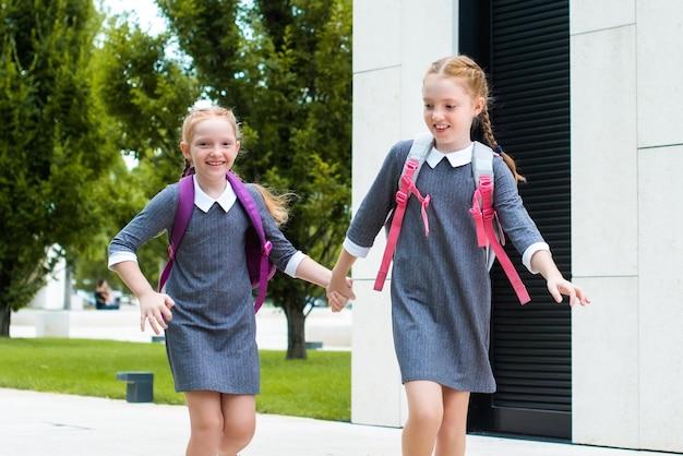 두 명의 귀여운 빨간 머리 여학생이 학교에 갑니다. 웃고, 채팅하고, 실행합니다. 교복을 입은 자매