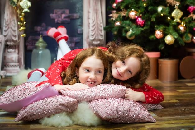 2人のかわいい赤毛の姉妹が新年のツリーでプレゼントを開きます