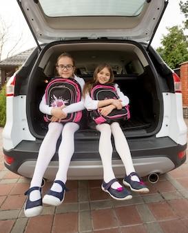 가방을 들고 열린 차 트렁크에서 포즈를 취하는 두 명의 귀여운 여학생