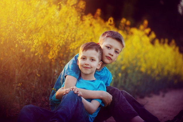 Two cute sibling boys hugging and having fun near the canola field.
