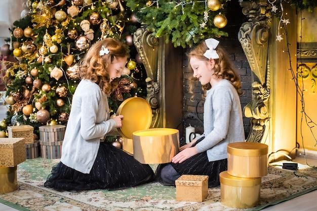 Две милые сестры открывают подарки у новогодней елки