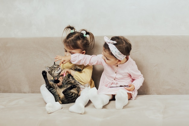 ぶち猫と遊ぶ2人のかわいい姉妹