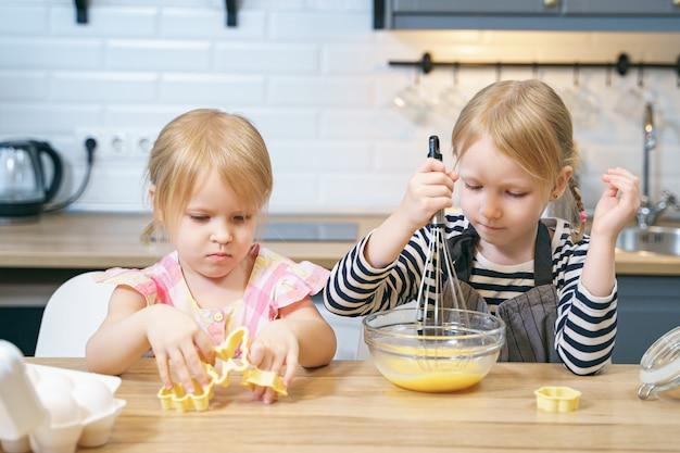 クッキー生地を準備する2人のかわいい姉妹。キッチンでママを助ける女の子