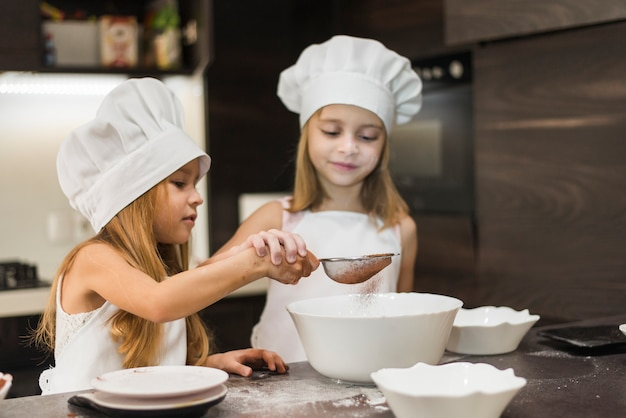 Two cute sisters sifting cocoa powder through strainer in kitchen