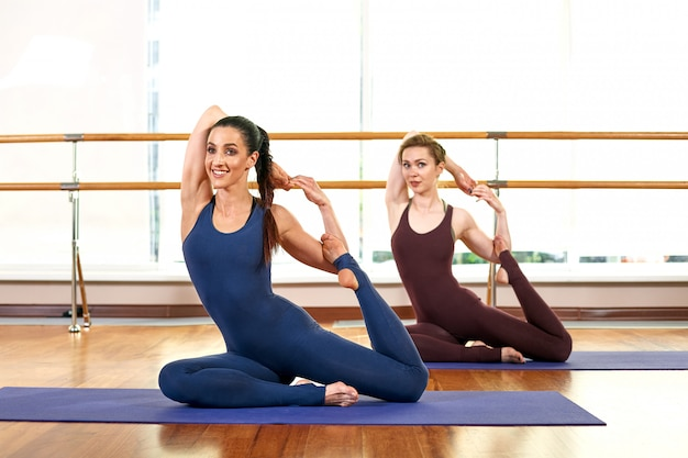 Two cute slim young women are doing the yoga pose while standing in a bright gym near a large window.