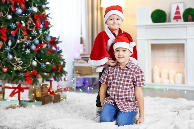 Two cute small brothers on christmas decoration background