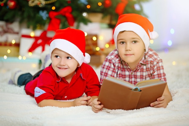 Two cute small brothers reading book on christmas decoration surface
