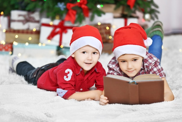 Two cute small brothers reading book on christmas decoration