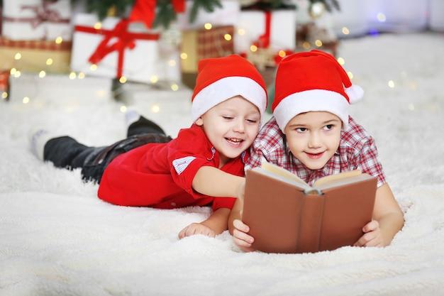クリスマスの装飾の背景に本を読んでいる2人のかわいい弟