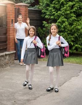 朝学校に家を出てバッグを持った2人のかわいい笑顔の女の子