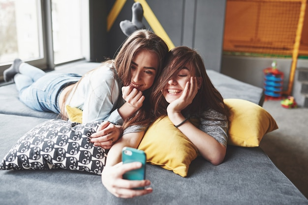 Two cute smiling twins sisters holding smartphone and making selfie. girls lie on the couch posing and joy