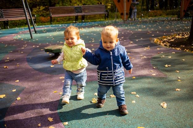 두 명의 귀여운 유아 소년과 소녀가 가을 공원을 산책하고 어린 시절부터 손을 잡고 우정을 나누다