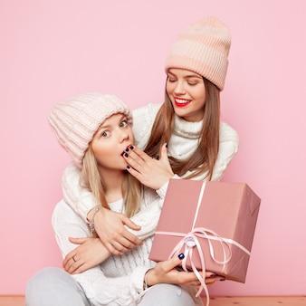 休日のために贈り物を与える赤い唇と帽子を持つ2つのかわいい女性。コンセプトクリスマスとネ