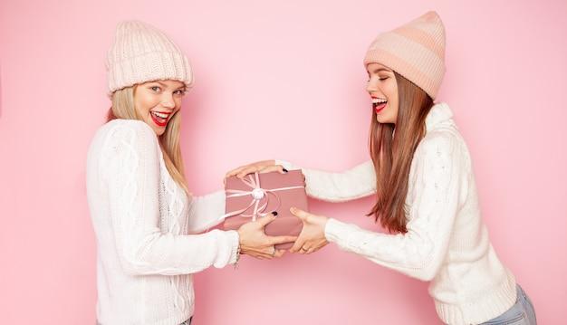 赤い唇と帽子との間に贈り物を共有している2つのかわいい女性。コンセプトクリスマス、
