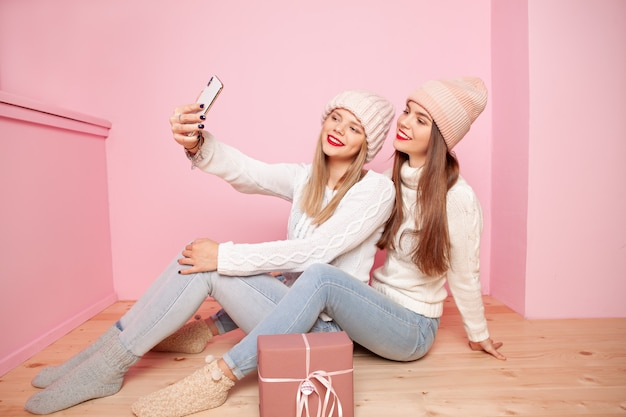 Two cute woman with red lips and hats sharing gift between themselves