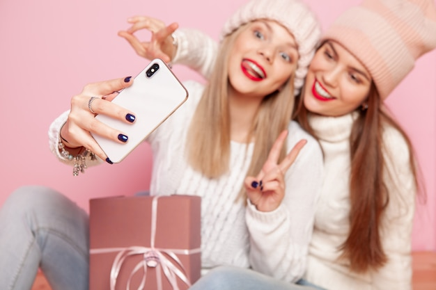 Two cute woman with red lips and hats sharing gift