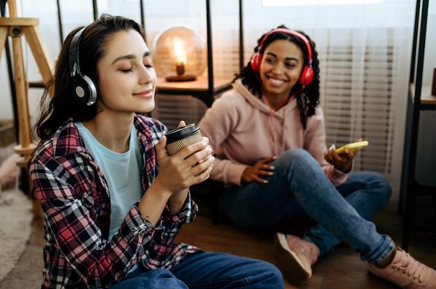 2 人のかわいい女性が家でコーヒーを飲みながら音楽を楽しんでいます。イヤホンをしたかわいいガールフレンドが部屋でくつろぎ、音の愛好家がソファで休んで、女性の友達が一緒にレジャーをする