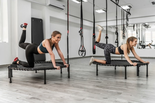 Two cute women jumping on trampoline, young fitness girls trains on a fitness studio
