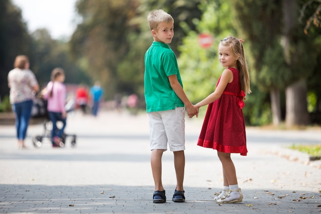Two cute young blond smiling children, girl and boy, brother and sister holding hands on blurred bright sunny summer park alley green trees bokeh . loving siblings relations .