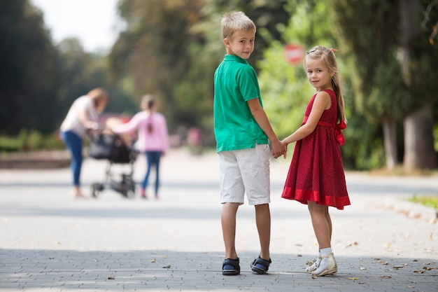 Two cute young blond smiling children, girl and boy, brother and sister holding hands